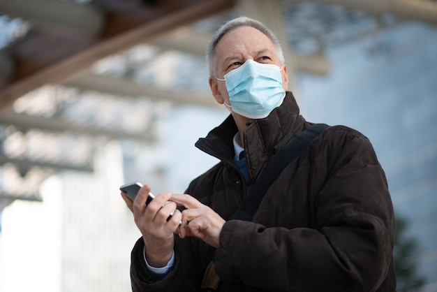 Koncepcja covid koronawirusa, zamaskowany starszy biznesmen używający swojego smartfona na zewnątrz