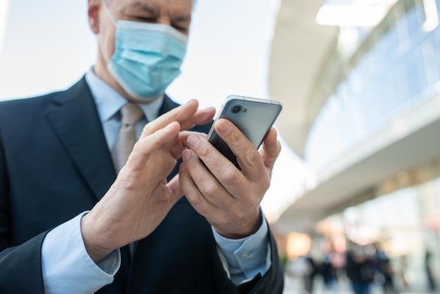 Koncepcja covid koronawirusa, zamaskowany starszy biznesmen za pomocą swojego smartfona na świeżym powietrzu w mieście