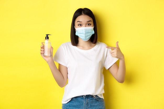 Koncepcja covid, opieki zdrowotnej i pandemii. azjatycka dziewczyna w masce na twarz od koronawirusa, wskazując palcem na dobry środek dezynfekujący do rąk, stojąca na żółtym tle.