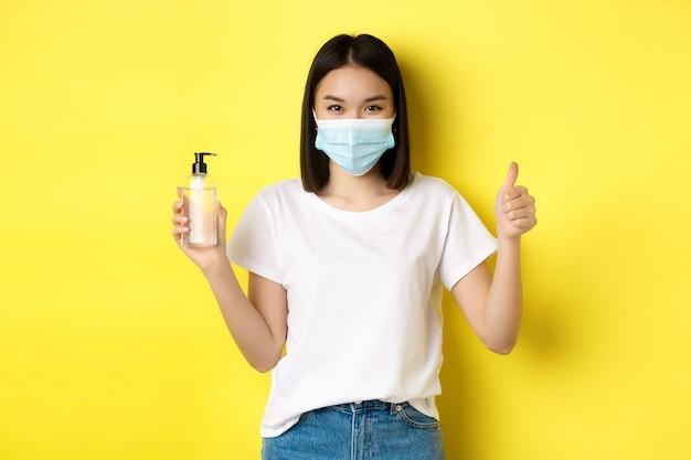 Koncepcja covid, opieki zdrowotnej i pandemii. azjatycka dziewczyna w masce na twarz z koronawirusa, pokazująca kciuk do góry i dobry odkażacz do rąk, stojąca na żółtym tle.