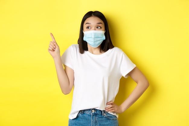 Koncepcja covid, opieki zdrowotnej i pandemii. azjatycka kobieta w masce medycznej i białej koszulce wskazując palcem w lewym górnym rogu logo, pokazująca promocję, żółte tło.