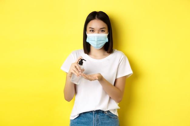 Koncepcja covid, opieki zdrowotnej i pandemii. śliczna azjatka w masce medycznej za pomocą środka dezynfekującego do rąk do dezynfekcji dłoni, stojąc na żółtym tle.