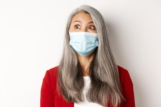 Koncepcja covid, pandemia i biznesowa. zbliżenie na elegancką azjatycką starszą kobietę wpatrującą się w lewy górny róg, ubrana w maskę medyczną z koronawirusa, białe tło.