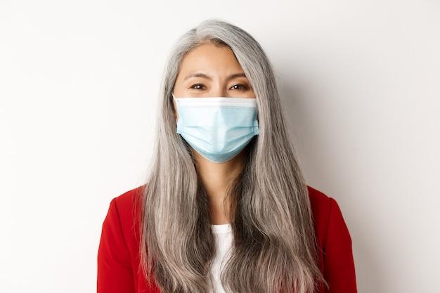 Koncepcja covid, pandemia i biznesowa. zbliżenie wesoły azjatycki starszy bizneswoman w masce medycznej uśmiechając się do kamery, białe tło.