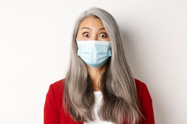 Koncepcja covid, pandemia i biznesowa. zbliżenie zaskoczony babcia azjatycka w masce medycznej podnosząc brwi, wpatrując się zdumiony na aparat, białe tło.