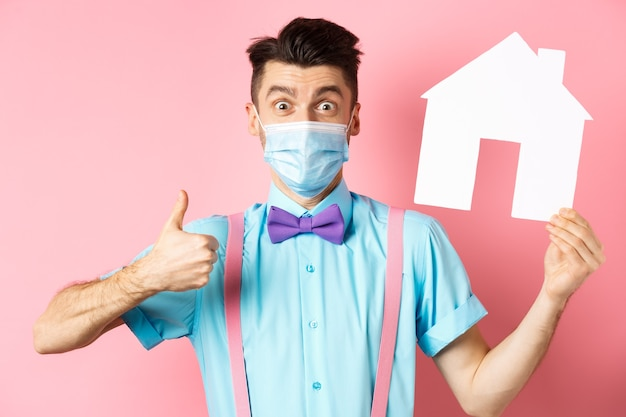 Koncepcja covid, pandemia i nieruchomości. zadowolony klient agencji pokazujący kciuk w górę i wycinankę z papierowego domu, w masce medycznej, stojący na różowym tle.
