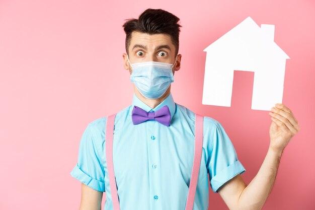 Koncepcja covid, pandemia i nieruchomości. zdezorientowany facet w masce medycznej szuka nieruchomości, pokazuje wycinek domu i patrzy na kamerę zmartwiony, stojąc na różowym tle.