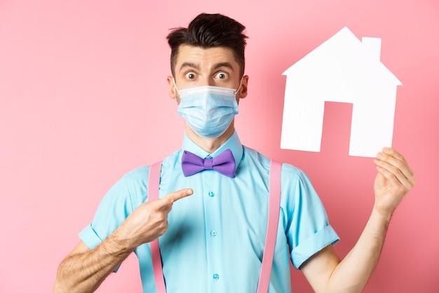 Koncepcja covid, pandemia i nieruchomości. zdziwiony mężczyzna w masce wskazujący na wycinankę z papierowego domu, stojący pod wrażeniem na różowym tle.