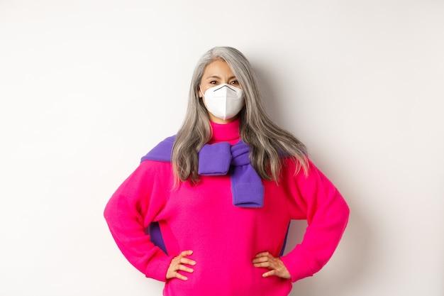 Koncepcja covid, pandemii i dystansu społecznego. pewna i wesoła azjatycka starsza kobieta w respiratorze, patrząca optymistycznie, uśmiechnięta i trzymająca się za ręce w talii, białe tło