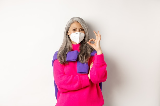 Koncepcja covid, pandemii i dystansu społecznego. wesoła i stylowa azjatycka starsza kobieta nosząca respirator przed koronawirusem, pokazująca znak ok, stojąca na białym tle.