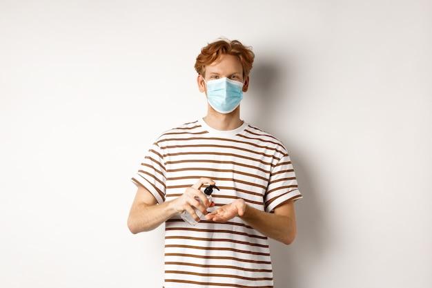 Koncepcja covid, wirus i dystans społeczny. nastolatek rudowłosy facet w masce na twarz czyści ręce środkiem odkażającym, używając środków antyseptycznych, stojąc na białym tle.