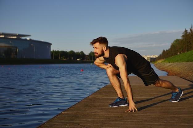 Koncepcja ćwiczeń fizycznych, aktywności, treningu, sportu i fitness. poziome ujęcie przystojny stylowy młody nieogolony mężczyzna ubrany w sportowe ubrania i buty do biegania pogrąża się na świeżym powietrzu w godzinach porannych