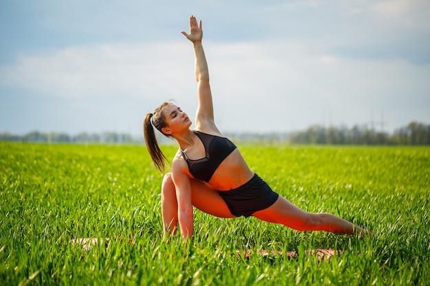 Koncepcja ćwiczeń zdrowego życia - sportowa kobieta fit ćwiczy asany jogi utthita parsvakonasana - rozszerzona pozycja kąta bocznego na zewnątrz w górach rano