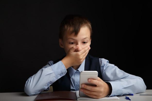 Koncepcja cyberprzemocy. zestresowany i zdenerwowany chłopiec w szkole z gadżetem na białym tle.