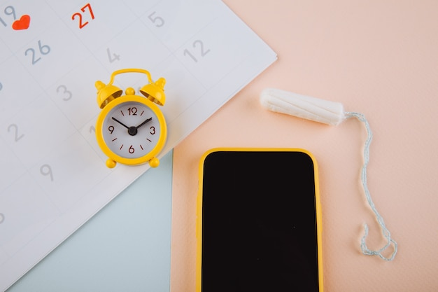 Koncepcja cyklu miesiączkowego. kalendarz na miesiąc ze znakami i aplikacją mobilną na ekranie smartfona.