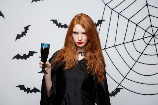 Koncepcja czarownica halloween - happy halloween czarownica trzyma kieliszek krwawego czerwonego wina na ciemnoszarym murem z nietoperzem i pajęczyną.