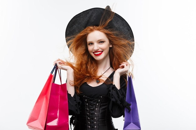 Koncepcja czarownicy halloween szczęśliwa wiedźma halloween uśmiecha się i trzyma kolorowe torby na zakupy na białej ścianie