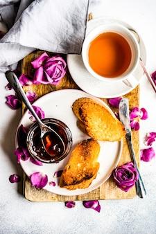 Koncepcja czas na herbatę z filiżanką herbaty i dżemem z płatków róży
