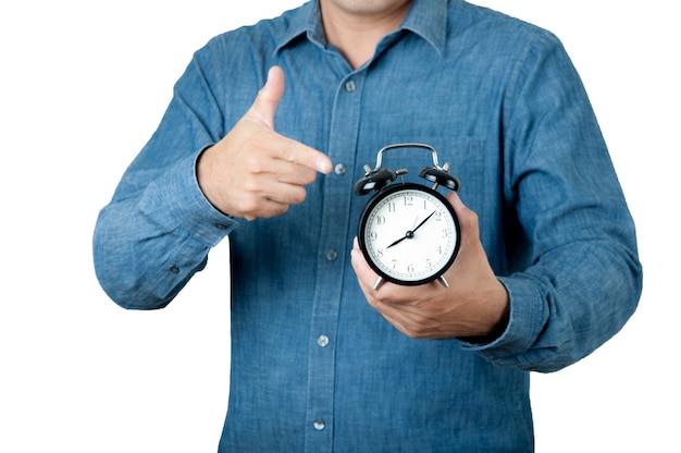 Koncepcja czasu. mężczyzna chwyta budzik w jego ręce dalej odizolowywa tło.