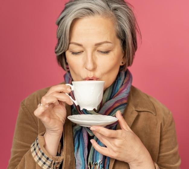 Koncepcja czasu na kawę. urocza siwowłosa kaukaska kobieta pije kawę w białej filiżance na różowym tle w studiu. z bliska strzał