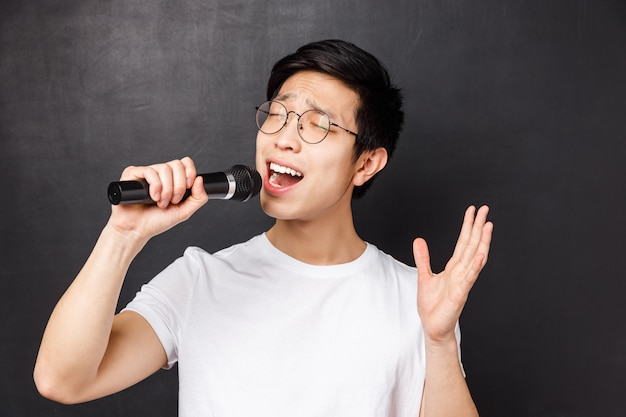 Koncepcja czasu wolnego, ludzi i muzyki. close-up portret namiętnego i beztroskiego azjatyckiego faceta lubi śpiewać piosenki, trzymać mikrofon i podnieść rękę, występować z przyjaciółmi na imprezie karaoke