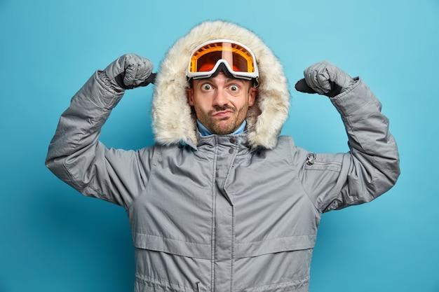 Koncepcja czasu zimowego. zaskoczony narciarz mężczyzna podnosi ręce i pokazuje swoje siły, aktywnie odpoczywa w górach jeździ na snowboardzie nosi odzież wierzchnią, wygląda poważnie.