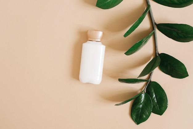 Koncepcja czystego piękna i organicznych kosmetyków do pielęgnacji ciała. butelka białego kremu leży na beżowym tle i gałęzi rośliny tropikalnej.