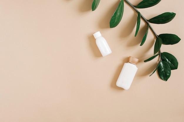 Koncepcja czystego piękna i organicznych kosmetyków do pielęgnacji ciała. butelki z białym kremem leżą na beżowym stole i gałęzi tropikalnej rośliny