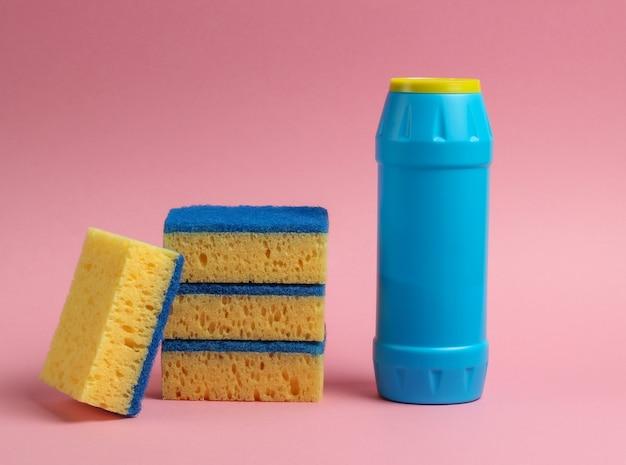 Koncepcja czyszczenia. butelka na detergent, gąbki na różowym pastelowym tle
