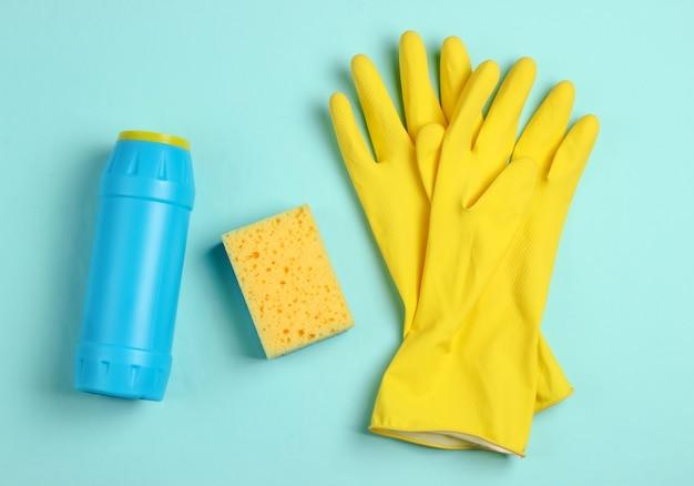 Koncepcja czyszczenia. butelki na detergent, gąbki, rękawiczki na niebieskim tle