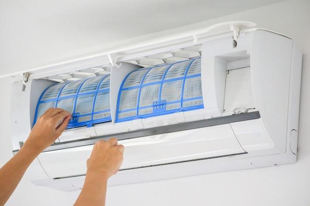 Koncepcja czyszczenia filtra klimatyzatora trzyma rękę człowieka