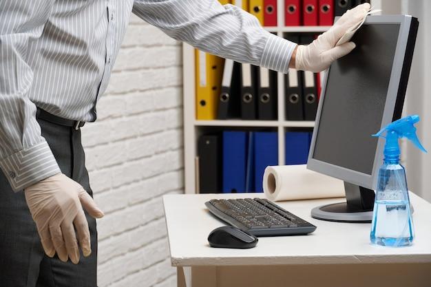 Koncepcja czyszczenia lub dezynfekcji biura - biznesmen czyści miejsce pracy, komputer, biurko, używa pistoletu natryskowego i papierowych serwetek. czyszczenie powierzchni z drobnoustrojów, wirusów i brudu.