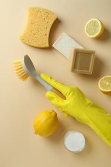 Koncepcja czyszczenia ręką w rękawicy trzymać pędzel na beżowym tle na białym tle