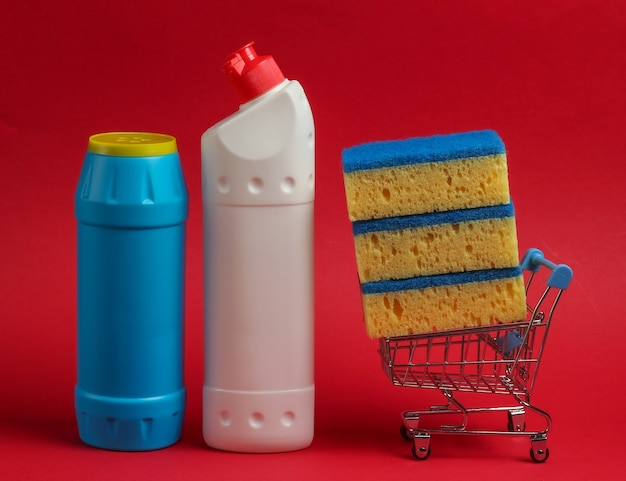 Koncepcja czyszczenia. wózek na zakupy z butelkami detergentu, gąbki na czerwonym tle