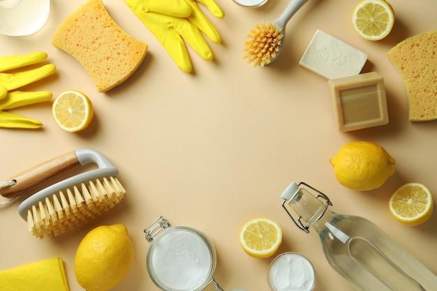Koncepcja czyszczenia z przyjaznymi dla środowiska narzędziami do czyszczenia i cytryn na beżowym tle na białym tle