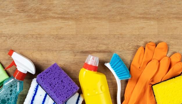 Koncepcja czyszczenia. zestaw środków czyszczących na drewnianym tle z miejsca na kopię, widok z góry