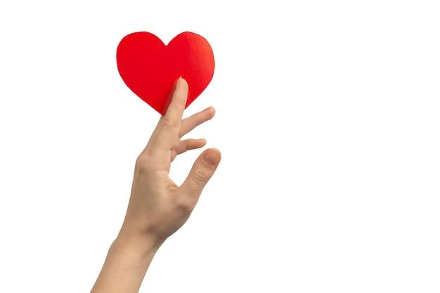 Koncepcja darowizny i miłości. ręka trzyma czerwone serce na białym tle na białym tle. skopiuj zdjęcie miejsca