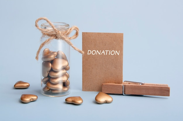 Koncepcja darowizny. szklana butelka ze złotymi sercami i kartka papieru z tekstem darowizny