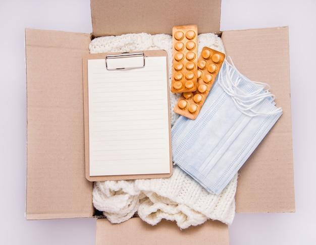 Koncepcja darowizny. w pudełku rzeczy, leki i środki ochrony indywidualnej.