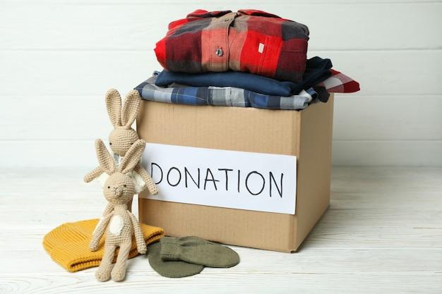 Koncepcja darowizny z pudełkiem darowizny na białym drewnianym stole