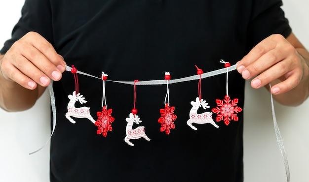 Koncepcja dekoracji domu bożego narodzenia, mężczyzna trzyma girlandę z ornamentem xmas na wystrój strony