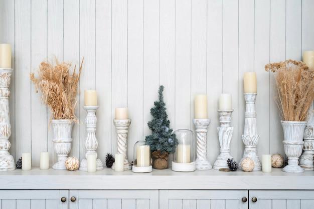 Koncepcja dekoracji wnętrz domu, gałąź kwiatów w małym wazonie i białe świece na stojaku