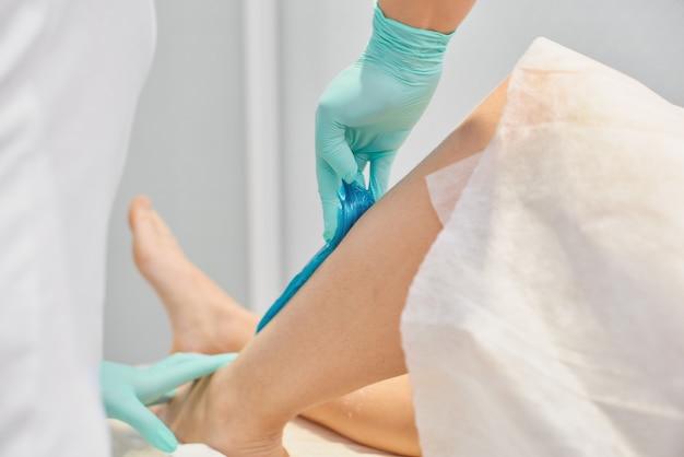 Koncepcja depilacji i urody - kosmetyczka depilująca nogi młodej kobiety płynnym cukrem w centrum spa. depilacja nóg turkusową pastą do shugowania