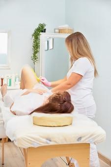 Koncepcja depilacji i urody - kosmetyczka depilująca nogi młodej kobiety płynnym cukrem w centrum spa. depilacja nóg żółtą pastą do shugowania