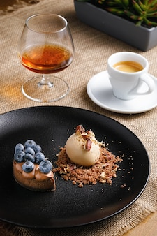 Koncepcja deser, lody i ciastko z jagodami na czarnym talerzu, kawa z brandy na stole.