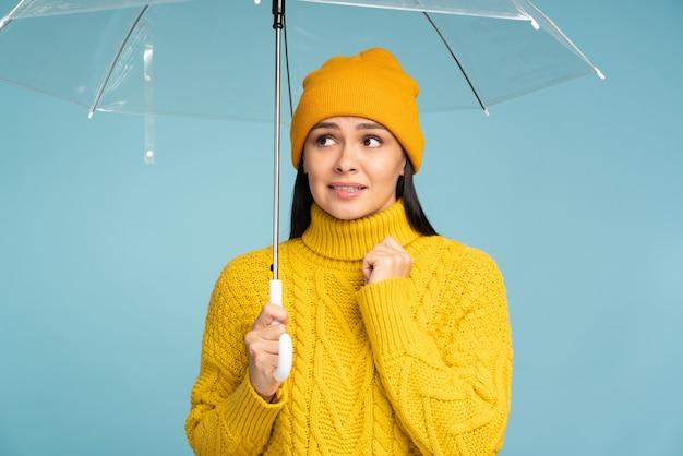 Koncepcja deszczowego dnia. portret pięknej smutnej kobiety trzymającej przezroczysty parasol i patrząc na białym tle nad niebieską ścianą. zdjęcie stockowe