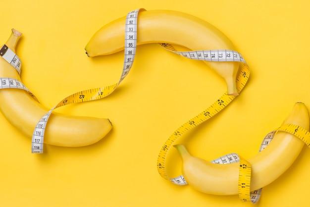 Koncepcja Diety, Fitness I Zdrowia Przedstawiona Przez żółtego Banana Owiniętego W Taśmę Mierniczą Na Białym Tle Na żółtym Papierze Premium Zdjęcia