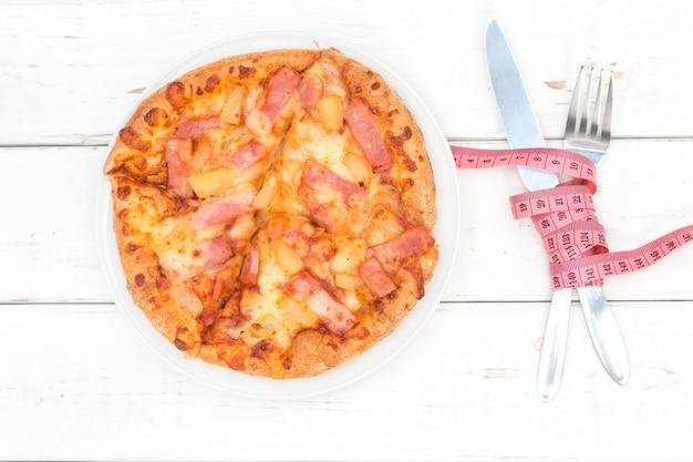 Koncepcja diety i fast foodów. hawajska pizza, widelec, nóż i taśma pomiarowa na drewnianym stole biały