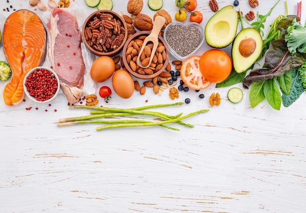 Koncepcja diety ketogenicznej niskowęglowodanowej składniki na wybór zdrowej żywności na białym drewnianym