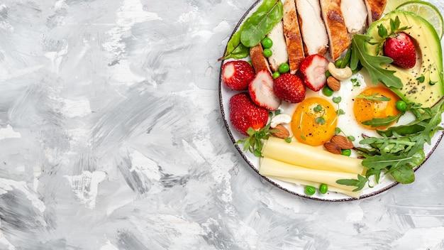 Koncepcja diety ketogenicznej o niskiej zawartości węglowodanów, jajko sadzone, awokado, truskawka, grillowany filet z kurczaka, ser, orzechy i rukola. koktajl detox, świeża zieleń, baner, miejsce na przepis menu na tekst, widok z góry,